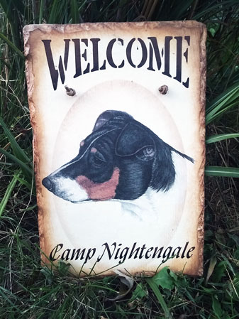 Welcome to Camp Nightengale sign with a picture of a terrior in the middle